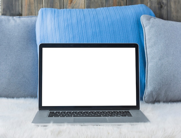 Laptop com tela branca em branco no sofá Foto gratuita
