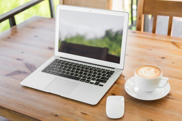 Laptop com tela em branco em uma mesa de madeira e uma chávena de café Foto gratuita