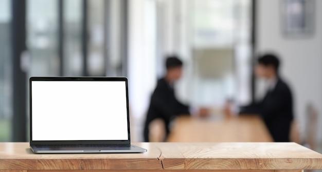 Laptop com tela em branco na mesa de madeira no escritório Foto Premium