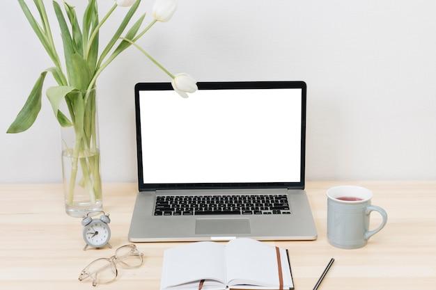 Laptop com tulipas brancas em um vaso na mesa de madeira Foto gratuita