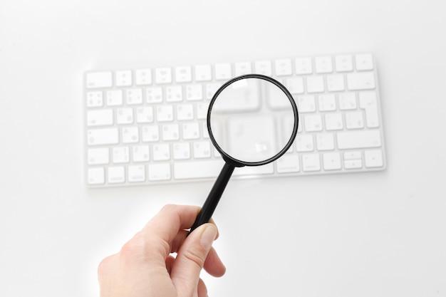 Laptop com uma lupa Foto Premium
