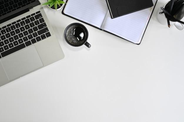 Laptop da mesa de escritório da vista superior, café, caderno com o lápis na tabela branca. Foto Premium
