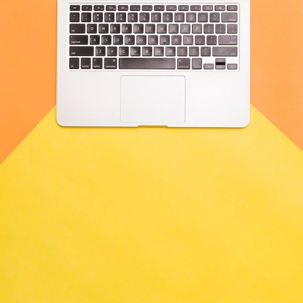 Laptop de configuração plana no fundo colorido Foto gratuita