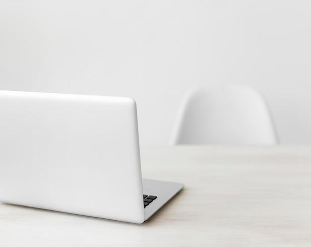 Laptop de escritório minimalista e cadeira Foto gratuita