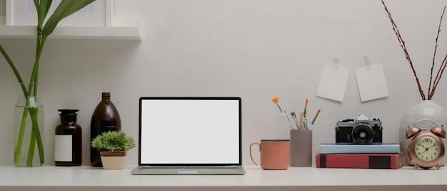 Laptop de tela em branco na mesa branca com suprimentos e decorações na sala de home office Foto Premium
