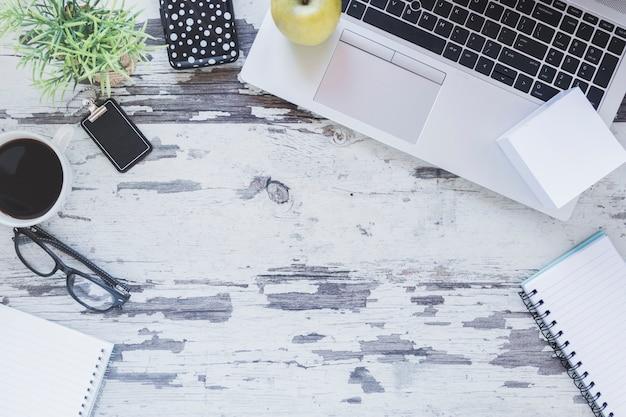 Laptop e artigos de papelaria perto de xícara de café e óculos Foto gratuita