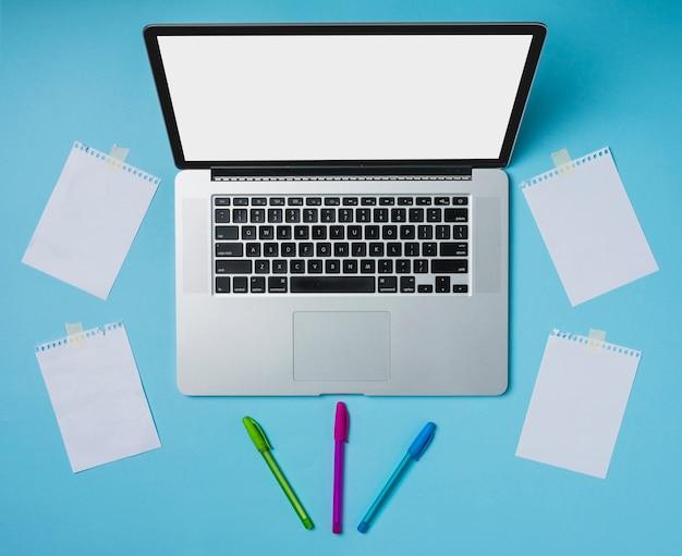 Laptop e canetas coloridas com papéis stucked com fita em pano de fundo azul Foto gratuita