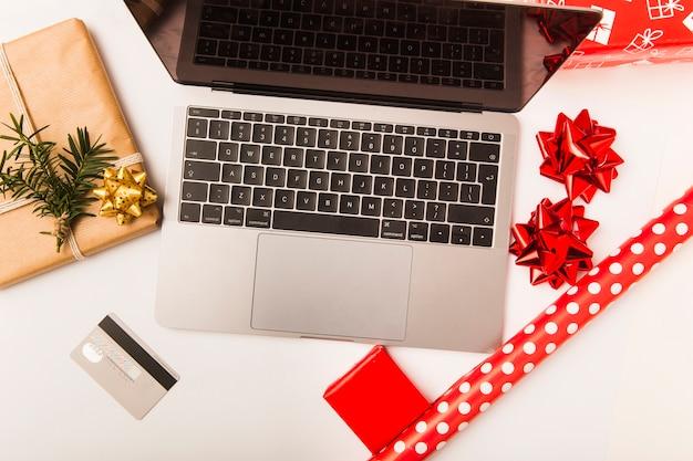 Laptop e cartão de crédito com presente embrulhado de natal na mesa Foto gratuita