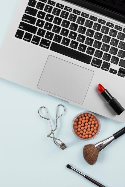 Laptop e ferramentas profissionais de maquiagem sobre fundo azul claro Foto gratuita
