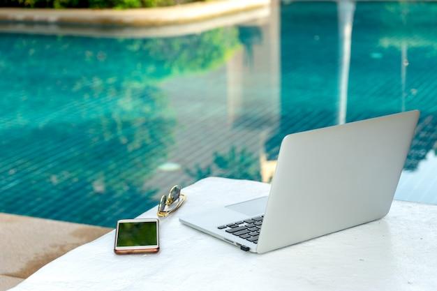 Laptop e smartphone perto da piscina, empresário moderno pode trabalhar em qualquer lugar. Foto Premium