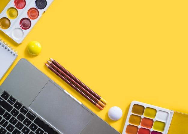Laptop e tintas na superfície amarela Foto gratuita