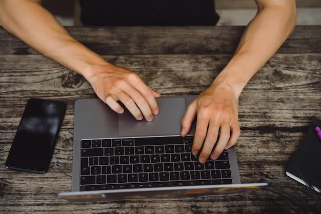 Laptop em uma mesa de madeira, mãos de um homem que trabalha em um computador Foto gratuita