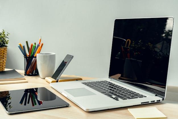 Laptop em uma sala de luz na mesa de trabalho com material de escritório Foto Premium