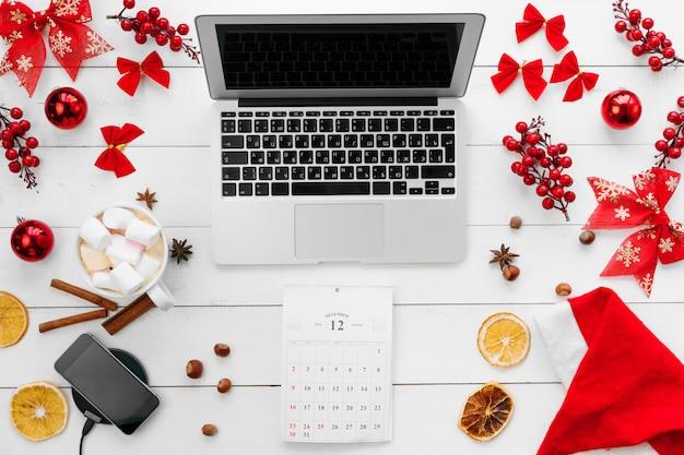 Laptop na mesa de madeira branca, cercada com decorações de natal vermelhas, vista superior Foto Premium