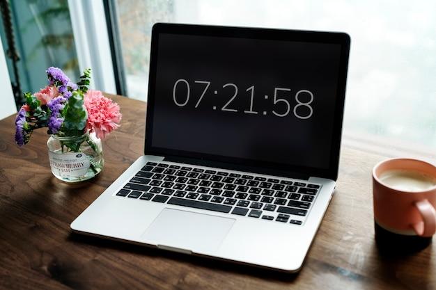 Laptop na mesa de madeira com cronômetro Foto gratuita