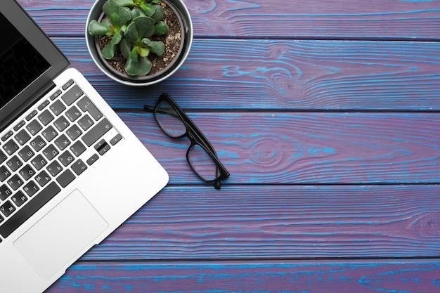 Laptop, óculos e planta em uma vista superior do fundo de madeira azul escuro Foto Premium