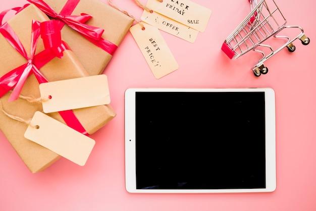 Laptop perto de carrinho de compras e caixas de presentes Foto gratuita