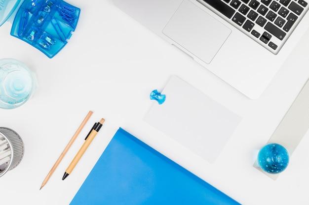 Laptop perto de papel, bola de brinquedo, lápis, caneta e clipes Foto gratuita
