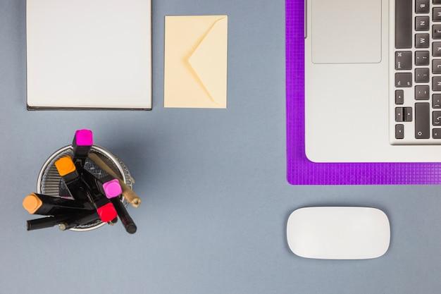 Laptop perto de papel, copo com canetas de feltro, carta e mouse de computador Foto gratuita