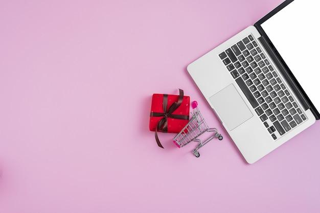 Laptop, perto, minúsculo, carrinho de compras, e, presente Foto gratuita