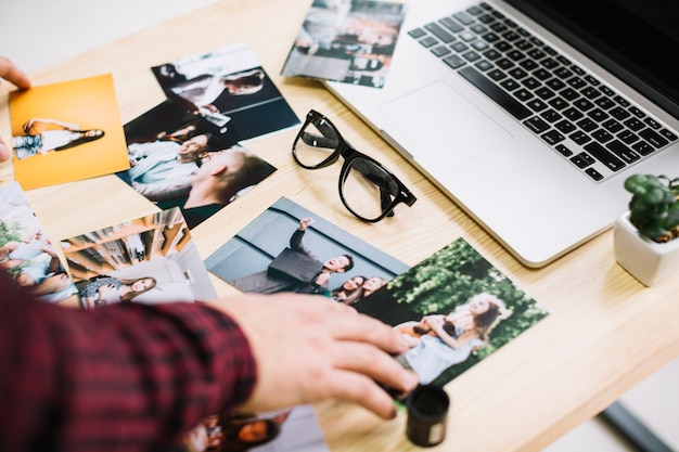 Laptop rodeado de fotos Foto gratuita