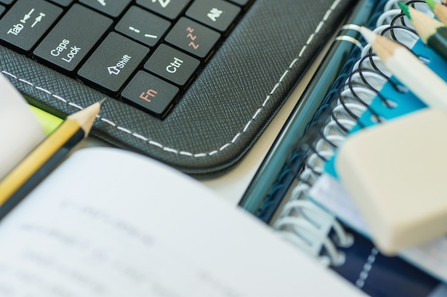Laptop tablet teclado aberto lápis de livro pilha de cadernos caneta no desktop branco Foto Premium