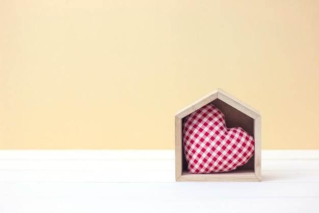Lar doce lar. conceito do dia de valentim com forma do coração na casa de madeira com espaço da cópia. Foto Premium