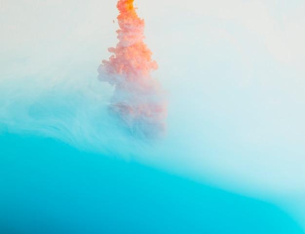 Laranja brilhante cair na neblina azul Foto gratuita