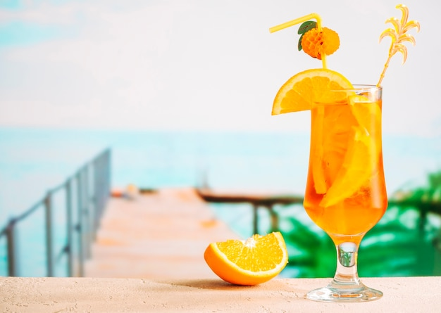 Laranja fatiada madura e copo de bebida cítrica suculenta apetitosa Foto gratuita