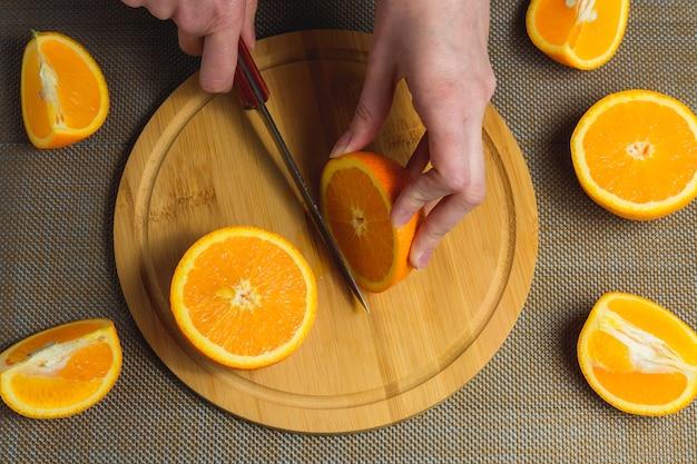 Laranja fêmea da fatia das mãos com a faca na placa de corte de madeira. frutos conceito saudável. vista do topo. Foto Premium