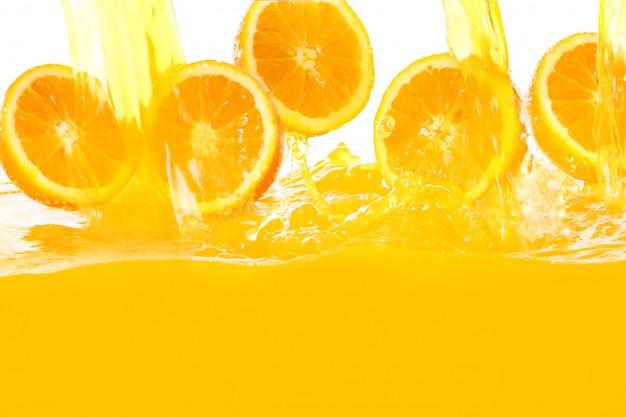Laranjas frescas caindo no suco Foto gratuita