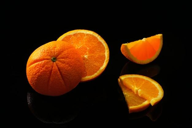 Laranjas frutas em uma superfície preta Foto Premium