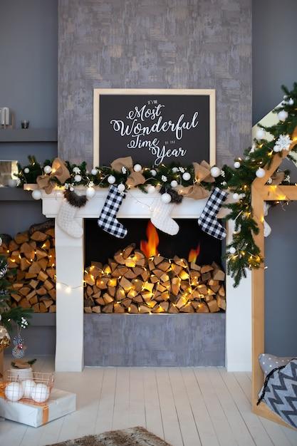 Lareira com meia de natal e presentes no interior da sala. a lareira branca está decorada com decorações de natal na sala de estar. meias vazias penduradas na lareira na véspera de natal. Foto Premium