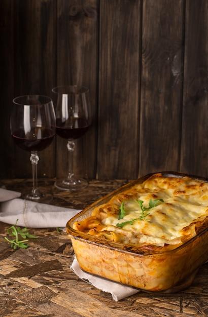 Lasanha de carne. vinho tinto no copo de vinho. lasanha italiana caseira com bolonhesa e bechamel Foto Premium