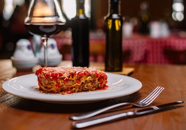 Lasanha italiana decorada com molho de tomate e parmesão ralado servido com vinho tinto Foto gratuita