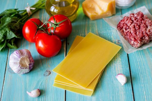 Lasanha, tomate, carne picada e outros ingredientes. fundo de madeira azul. cozinha italiana. Foto Premium