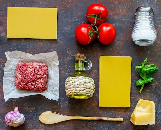 Lasanha, tomate, carne picada e outros ingredientes. fundo escuro. cozinha italiana. Foto Premium