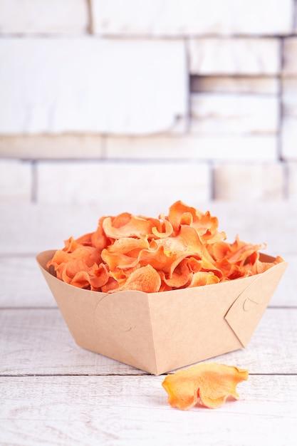 Lascas de cenoura desidratadas secas. delicioso lanche ecológico e orgânico para toda a família. conceito de alimentação saudável. Foto Premium