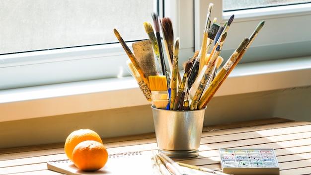 Lata metálica com escovas em uma mesa Foto gratuita