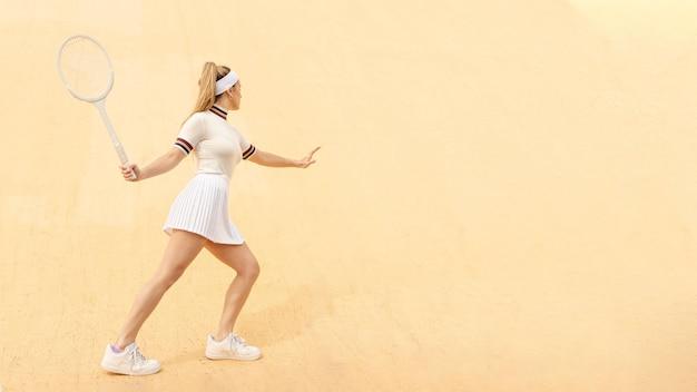Lateral batendo na posição de jogador de tênis de bola Foto gratuita