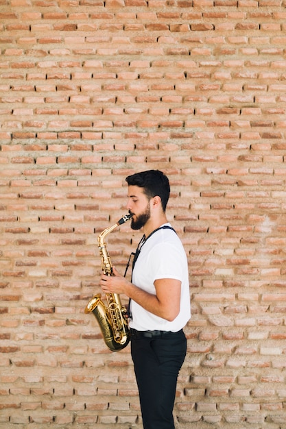 Lateralmente, homem, tocando, saxofone, com, tijolo, parede, fundo Foto gratuita