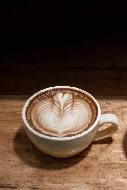Latte art café na xícara de café na mesa de madeira em preto Foto Premium