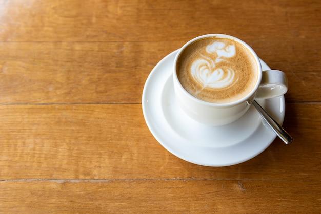 Latte art (forma de coração) na mesa de madeira com espaço de cópia Foto Premium