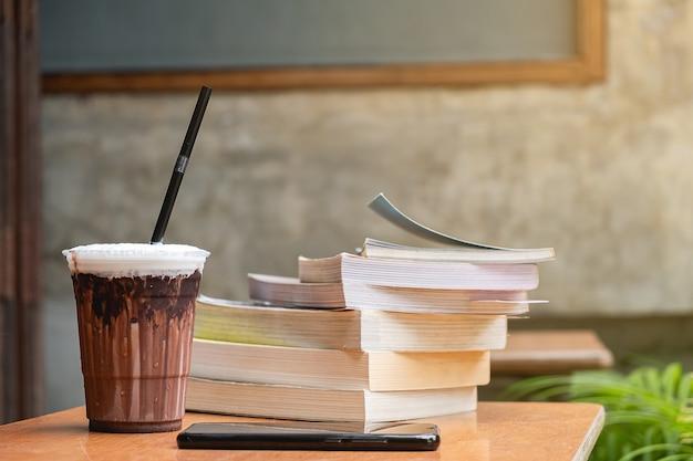 Latte gelado e livro na mesa, educação e conceito de negócio, copie o espaço Foto Premium
