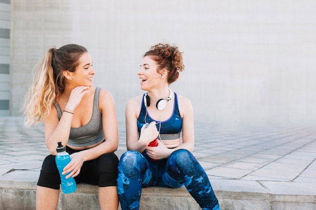 Laughing girls in sportswear sentado na rua Foto gratuita