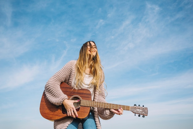 Laughing mulher tocando guitarra na natureza Foto gratuita