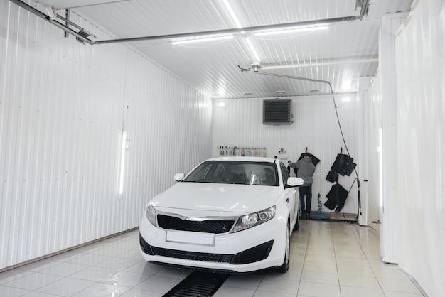 Lavagem moderna com espuma e água de alta pressão de um carro branco. lava-jato. Foto Premium