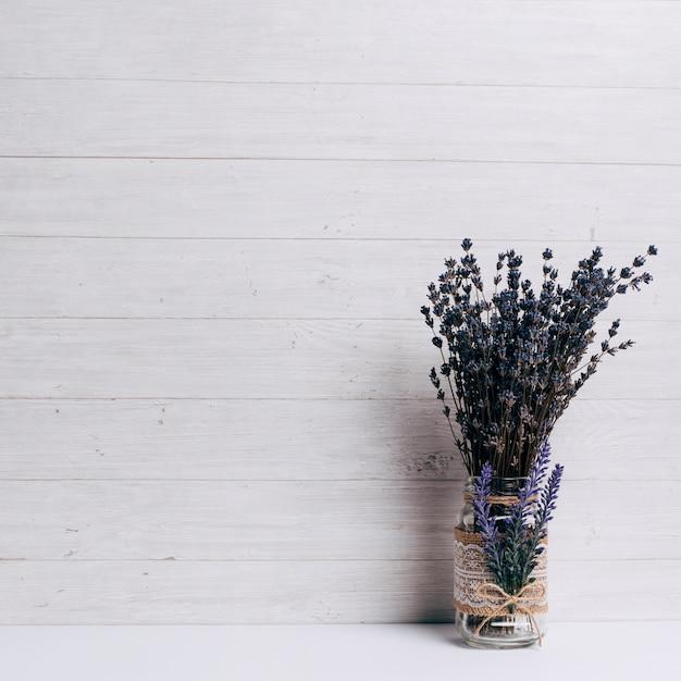 Lavanda no copo na mesa contra o fundo de madeira Foto gratuita