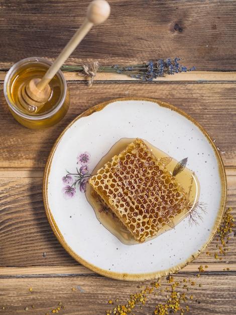 Lavanda; pote de mel com mel de madeira e pólen de abelha na mesa de madeira Foto gratuita