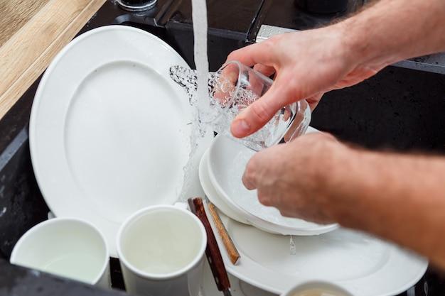 Lavando pratos - homem com as mãos em luvas enxaguando vidros com água corrente na pia. Foto Premium
